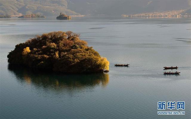 """11月12日,游客在泸沽湖乘坐小木船观景。地处滇川交界处的泸沽湖有""""高原明珠""""之称,湖面海拔2690米,面积约50平方公里。绝美的湖光山色自然景观和神秘的摩梭文化吸引不少游客前来观光。"""