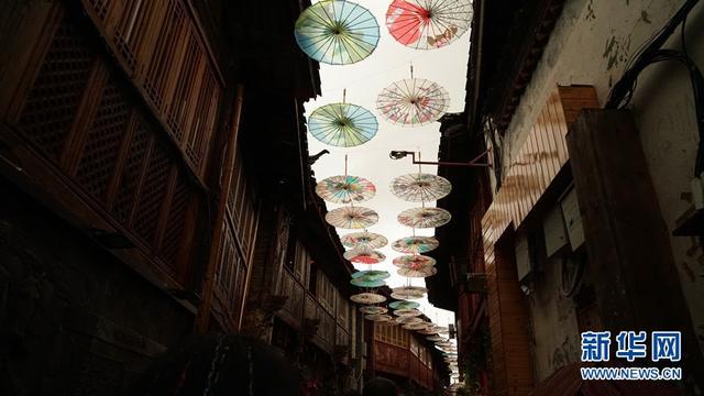 近日,丽江古城光义街现文巷街道上空挂起了多把油纸伞,引来游客驻足观赏拍照。入夜,古城下起小雨,撑伞的行人与倒挂的油纸伞互相呼应,更显风趣。(新华网 丁凝 摄影报道)