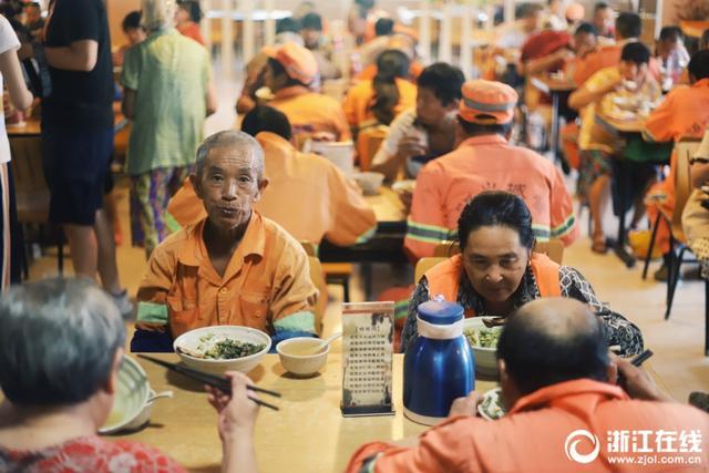 """2018年8月2日中午11时,在杭州市勾庄好运路雨花斋餐厅,市民们持续井然地等候免费午餐,当日供应的免费午餐有红烧豆腐干、炒花菜、长豇豆和毛豆。常言道,""""天下没有免费的午餐"""",这家餐厅从2013年开始免费提供素食,不收一分钱,吃饭管饱。目前每天来店里的人,有近250人左右,多数是环卫工人和年长的务工者,还有附近小区的居民,只要是生活困难需要帮助的人都可来用餐。拍摄者:胡浩然、李翔"""