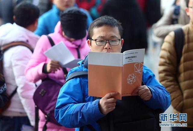 12月24日,在天津南开大学考点,考生在等候入场时复习。新华社发(刘东岳 摄)