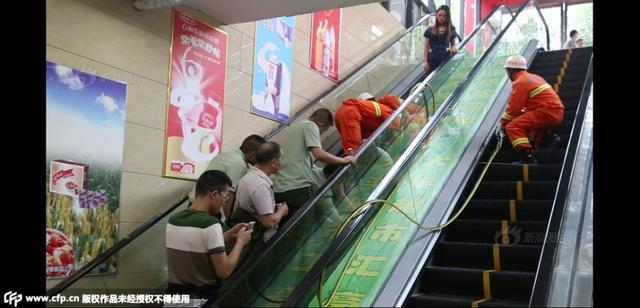 2015年9月15日下午4时左右,重庆市秀山县一部扶梯发生了这起意外,一名3岁左右的小女孩左手臂被卡,直到消防官兵将扶梯强行扩张后,顺利将小孩手臂取了出来,并迅速交由现场医护人员检查治疗。供图:CFP
