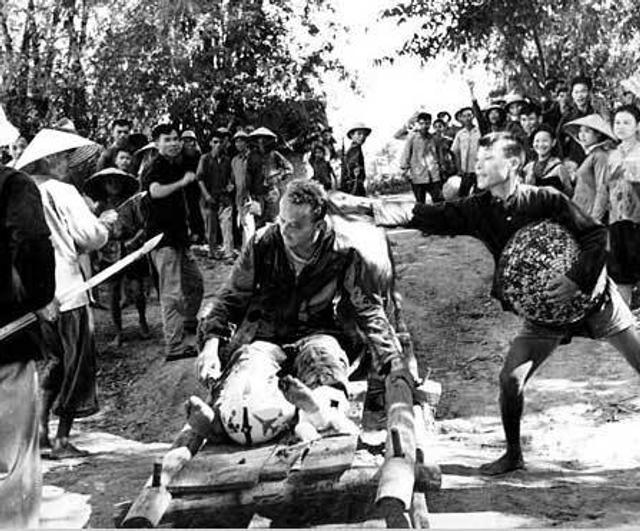 越南战争,简称越战,又称第二次印度支那战争。战争中,美军利用空中优势,多次派出战机对越南进行轰炸。图为越南村民在羞辱腿部受伤被俘的美国空军飞行员Willard S.Giedon(1966.8.7)
