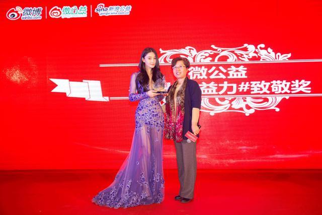 """中国妇女发展基金会秘书长助理胡金霞女士为张馨予颁发了微公益""""#星光公益力#致敬奖""""奖杯。"""