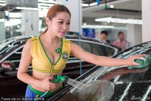 2014年7月13日,在浙江省义乌市市区一洗车行内,身着各国球队队服的美女,妩媚地洗着豪车,吸引了大批顾客。