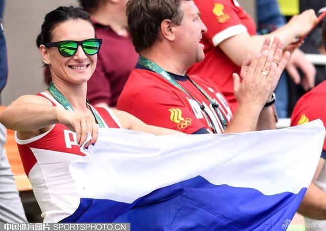 里约当地时间2016年8月16日,因国际田联对于俄罗斯田径队禁赛制裁而无法参赛的女子撑杆跳高名将伊辛巴耶娃,来到花样游泳女子双人比赛的水池边为俄罗斯选手加油助威。