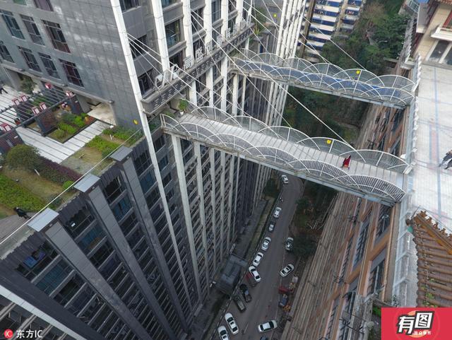 """2017年3月16日,重庆渝中区一栋大楼从22层架起两座平行的天桥,连接对面的魁星楼广场地面。这两座约23米长的空中连廊离地达68.5米,站在天桥向下看去可谓""""深不见底""""。水平天桥一端是22层楼,另一端是地面,许多网友直呼:""""重庆就是一座3D魔幻城市。"""""""